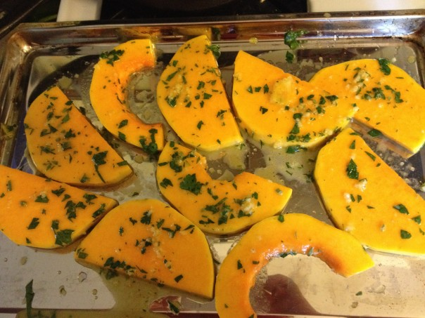 Squash rounds on baking sheet ready to go into the oven, covered with garlic, oil, herb and orange juice marinade
