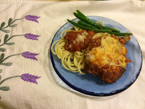 Plated Eggplant Parmesan with fresh pasta and green beans.